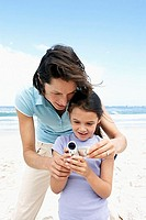 Mother and daughter 6-8 standing on beach, using digital video camera