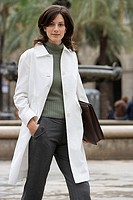 Businesswoman in polo neck jumper and white coat walking in plaza, carrying briefcase, portrait