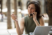 Businesswoman sitting at pavement cafe table with laptop, using mobile phone, smiling