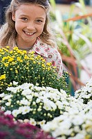 Girl 7-9 standing beside colourful flowers in garden centre, smiling, close-up, portrait