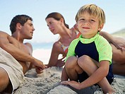 Family sitting on beach, focus on boy 5-7 crouching in foreground, smiling, portrait
