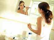 Teenage girl 15-17 looking at reflection in bathroom mirror, applying make-up with brush tilt