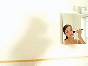 Teenage girl 15-17 looking at reflection in bathroom mirror, applying make-up with brush (thumbnail)