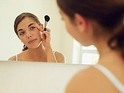 Teenage girl 15-17 looking at reflection in bathroom mirror, applying make-up with brush