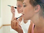 Two teenage girls 15-17 applying make-up in bathroom, close-up, profile