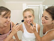 Teenage girls 15-17 applying make-up to friend's face, smiling, close-up