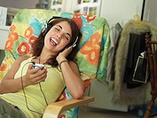 Teenage girl 15-17 sitting in armchair at home, listening to MP3 player, singing, eyes closed
