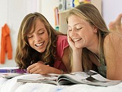 Two teenage girls 15-17 lying on bed, reading magazine, smiling, close-up