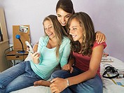 Three teenage girls 15-17 sitting on bed, using mobile camera phone, smiling