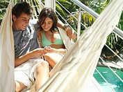 Teenage couple 15-17 relaxing in hammock on balcony, listening to MP3 player, smiling