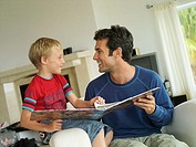 Father and son 5-7 looking at photo album at home, sitting in chair, face to face, smiling tilt