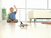 Boy 5-7 playing with toy plane at home, sitting on floor with hand raised, smiling, surface level