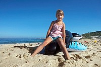Girl 4-6 sitting on inflatable toy whale on beach, smiling, portrait