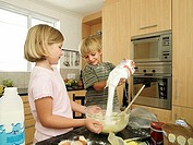 Boy 5-7 and girl 6-8 making cake mix in kitchen, boy pouring flour into glass bowl, smiling