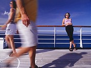 Woman standing on deck of cruise ship, people passing by