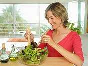 Woman tossing salad with olive oil and balsamic vinegar dressing in bowl in kitchen, smiling