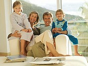 Two generation family relaxing in armchair beside balcony sliding doors, smiling, portrait