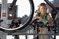 Young woman shopping for new bike in bicycle shop, view through bike frame, smiling, portrait