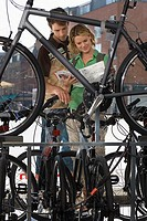 Young couple shopping for new bike in bicycle shop, looking at brochure, view through bike frame