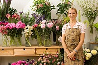 Florist in apron standing in front of display in flower shop, smiling, front view, portrait (thumbnail)