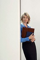 Blonde businesswoman standing beside office window, holding diary and folder, smiling, portrait