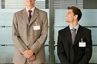 Short businessman looking up at tall businessman, standing side by side, smiling, front view