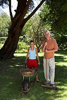 Grandfather and granddaughter 9-11 standing with wheelbarrow and rake in garden, smiling, portrait