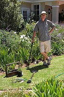 Senior man standing on lawn, gardening, leaning on garden fork, hand on hip, smiling, portrait