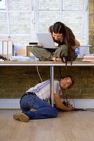 Man plugging cable into office floor socket below desk, woman sitting on top of desk, using laptop