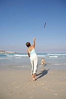 Woman throwing stick on beach, dog chasing, rear view, sea in background