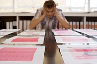 Man looking at various designs arranged on large table in office, surface level