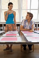 Young man and woman looking at various designs arranged on large table in office, surface level