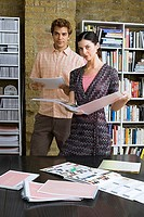 Young man and woman standing in office, looking at designs in folder, portrait