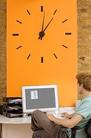 Young man sitting at desk in office beside large orange wall clock, looking at computer, rear view