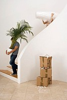 Couple moving house, man carrying large pot plant down staircase, woman carrying dust sheet, profile