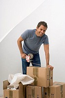 Man moving house, using duct tape dispenser to seal cardboard box, smiling, portrait