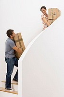 Couple moving house, ascending staircase, carrying boxes, woman looking over shoulder, smiling