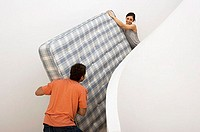 Couple moving house, carrying king size matress on staircase, smiling