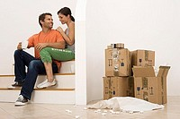 Couple moving house, taking tea break at bottom of staircase near stack of boxes, smiling