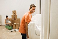Couple moving house, man lifting white sofa through doorway, woman packing boxes in sparse room