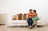 Couple moving house, embracing on white sofa wrapped in plastic sheet beside boxes, smiling