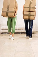 Couple moving house, carrying stack of cardboard boxes, side by side, low section, front view