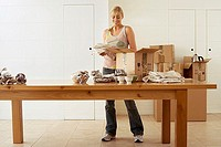 Woman moving house, packing crockery in cardboard boxes on dining room table, smiling, front view