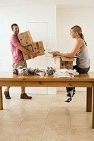 Couple moving house, woman packing crockery in box on dining room table, man carrying sealed boxes