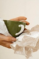 Woman moving house, wrapping crockery in paper, side view, close-up of cup