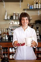 Waitress serving behind counter in cafe, holding large mug, spoon and napkin, smiling, portrait