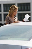 Businesswoman standing beside car, reading document, side view