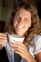 Young woman drinking latte in cafe, smiling, close-up, portrait