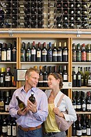 Couple shopping in off-licence, man holding bottles of wine, smiling, shelf display in background