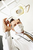 Dentist in surgical mask adjusting surgical light in dental surgery, low angle view, portrait tilt